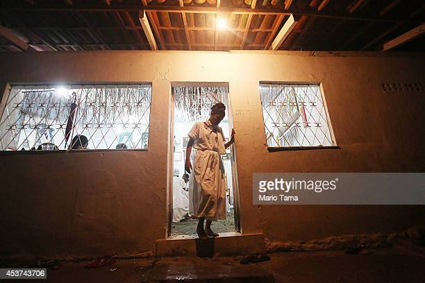 A practitioner walks out of a house of worship following a Candomble ceremony on August 17 2014 in Cachoeira Brazil Candomble is an AfroBrazilian...