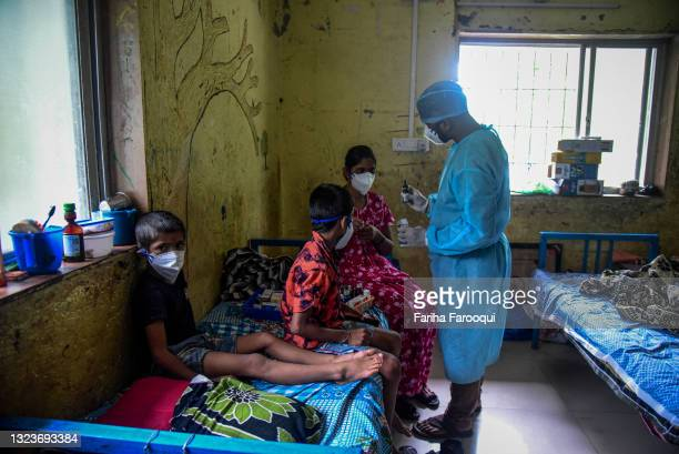 Pradip Salave Shramajeevi, a healthcare worker, talks to patients who have contracted the coronavirus about their medication inside a school which...
