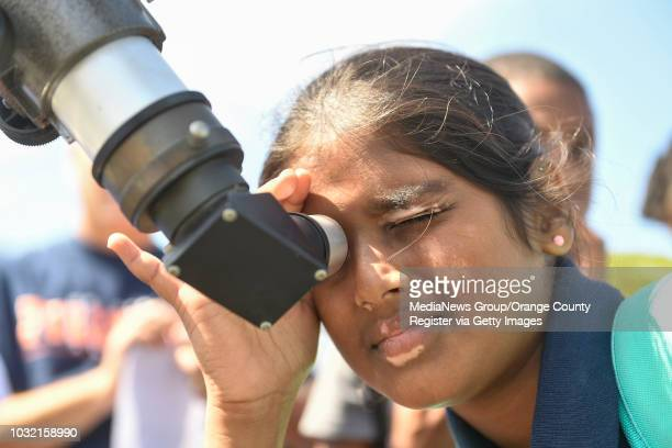 Pragati Muthuselvan looks at the partial partial solar eclipse through a telescope at Lexington Junior High School in Cypress California on Monday...