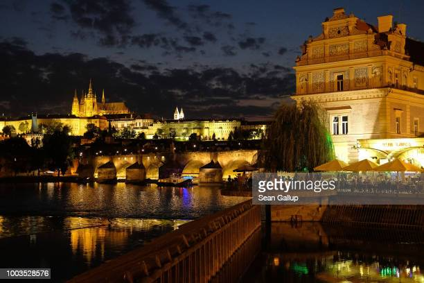 Prague Castle and the Charles Bridge stand illuminated over the Vltava River as people relax at an outdoor restaurant on July 20 2018 in Prague Czech...