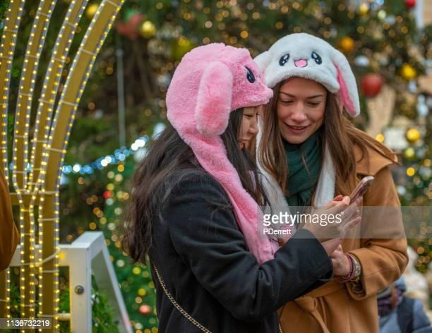 プラハのクリスマスマーケット。ノベルティビーニーを持つ2人の女性が自分の携帯電話をチェックします。