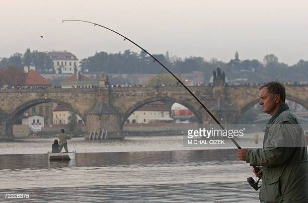 Fishermen fish on the banks of the Vtava river on Strelecky island in Prague 20 October 2006 after thousands of fishes were released in the river...