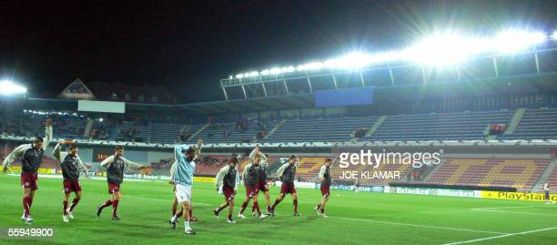 Prague, CZECH REPUBLIC: Football players of Sparta Prague warm up backgrounded by an empty Sparta Prague tribune shortly prior the UEFA Champions...