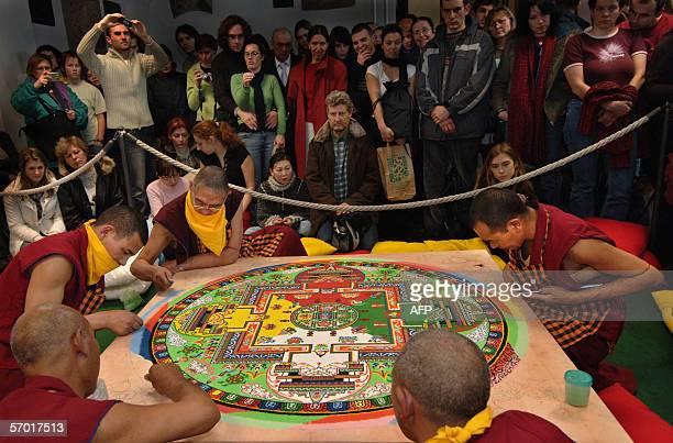 Tibetan monks from India work on a mandala of coloured sands in the Prague Museum 07 March 2006 The monks will throw this mandala into the Vltava...