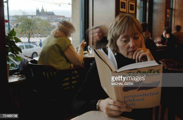 TO GO WITH AFP STORY A woman reads the first publication in Czech of Milan Kundera's novel The Unbearable Lightness of Being in Cafe Slavia in Prague...