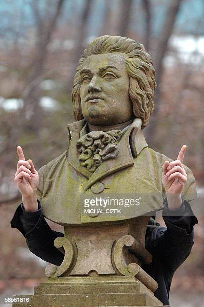 TO GO WITH AFP STORY AFP EntertainmentmusicanniversaryMozartCzech An unidentified young man standing behind the bust of WA Mozart jokes while trying...