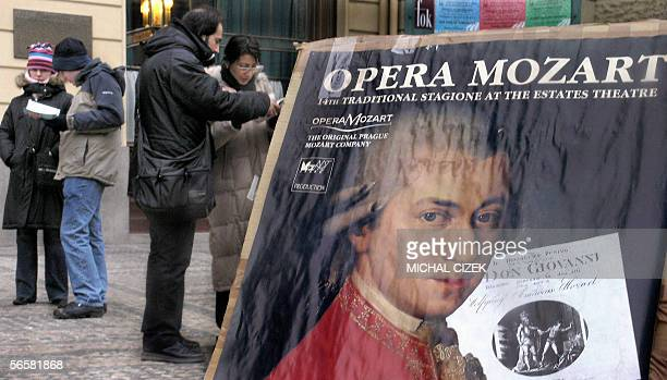 TO GO WITH AFP STORY AFP EntertainmentmusicanniversaryMozartCzech Tourists search information next to a Mozart's poster inviting them to see the...