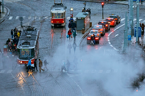 Prague street scene with trams, traffic and pedestrians on cobblestone road and large smoke cloud - gettyimageskorea