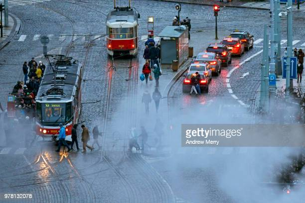 Prague street scene with trams, traffic and pedestrians on cobblestone road and large smoke cloud