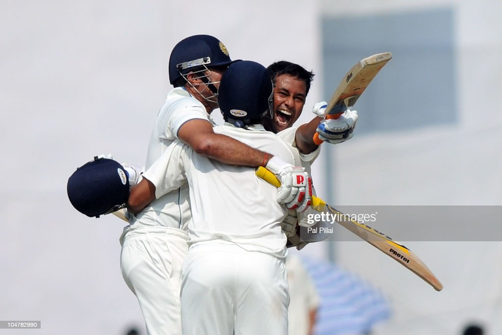 Pragyan Ojha of India celebrates his team`s victory with teammates VVS Laxman and Suresh Raina on day five of the First Test match between India and..