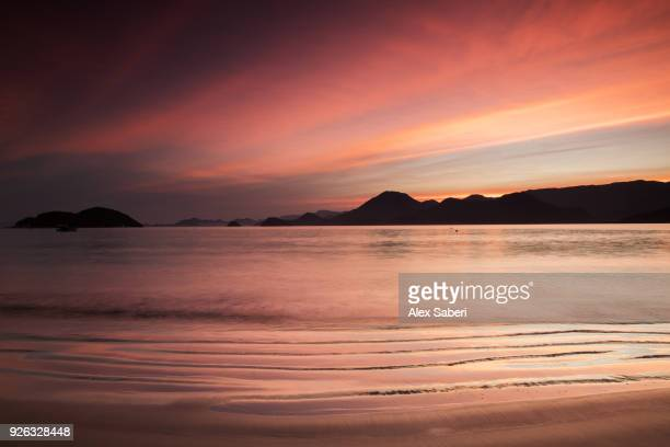A dramatic red sunset on Almada beach in the Atlantic rainforest in Ubatuba, Brazil.