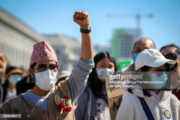 Prakash Thapa, left, native of Nepal who lives in Fremont, fists pump as he listens to speakers during an anti-Asian American hate march and rally at...