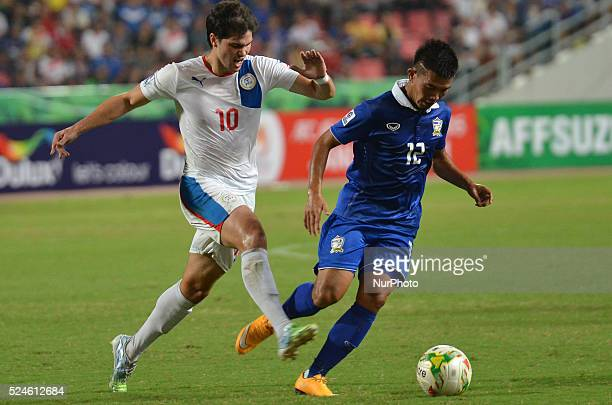 Prakit Deeporm of Thailand is closed down by Phil Younghusband of Philippines during the AFF Suzuki Cup 2014 semifinals 2nd match between Thailand...