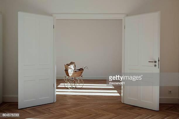 Pram in empty room, open doors