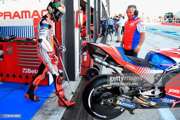 Pramac Racing's Italian rider Francesco Bagnaia uses a stick as he walks up to his bike during the third free practice session ahead of the San...
