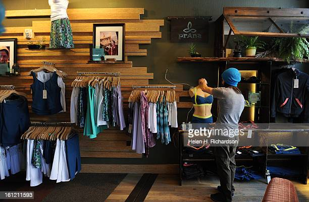 Prana store employee Ryan Silven works on displays in the Boulder store Three yoga apparel retailers are preparing to open new stores in Cherry Creek...