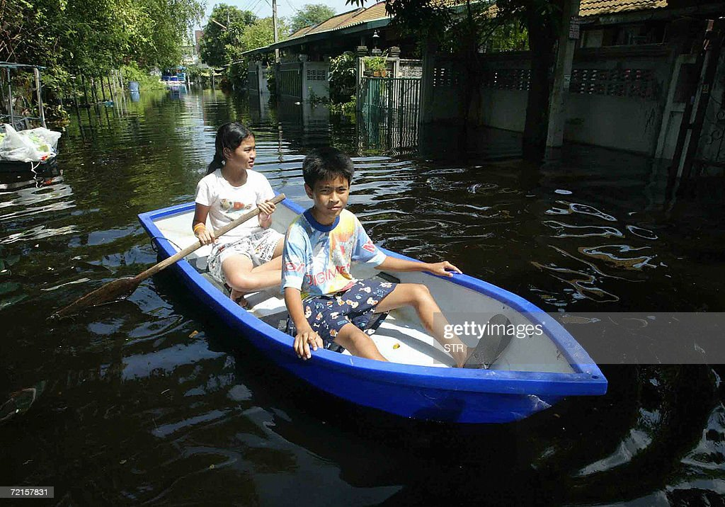 Residents paddles through a flooded village street in Prathumthani povince suburban Bangkok, 13 October 2006. The death toll from severe flooding across Thailand rose to 47, the government said 13 October even as waters began to recede in northern provinces.