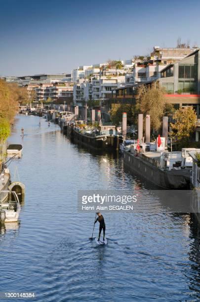 Pratique du paddle le long du bras de Seine de la Promenade des Chartreux à Issy-les-Moulineaux, quartier résidentiel du quai de Stalingrad, 18...
