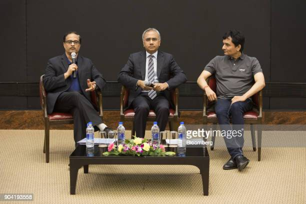 Pravin Rao chief operating officer of Infosys Ltd left speaks as he sits beside Salil Parekh chief executive officer of Infosys Ltd center and...
