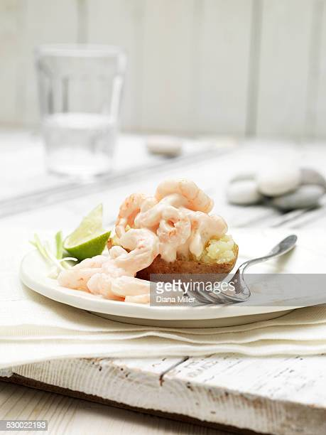 Prawn cocktail jacket potato with slice of lime and spring onion garnish