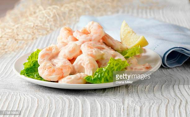 Prawn cocktail with lemon, lettuce and rose marie sauce on white wooden surface with fishing net