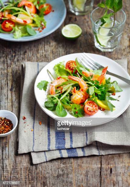Prawn salad on a white plate on a wooden table