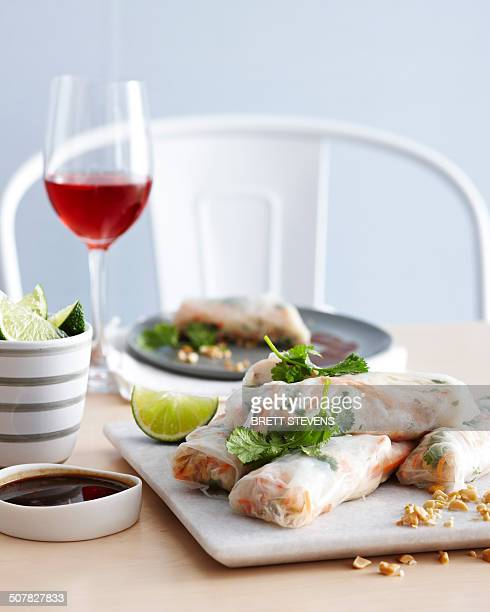 Prawn spring rolls on chopping board with tamarind