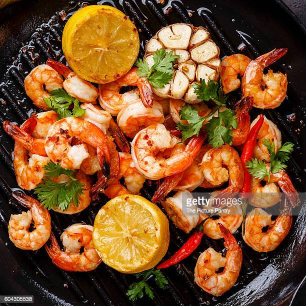 Prawns Shrimps roasted on frying grill pan with lemon and garlic close up