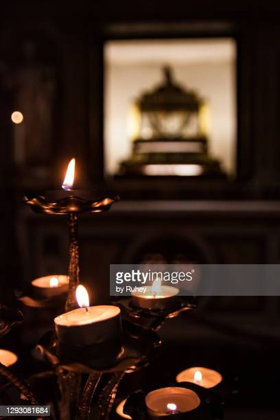 prayer candles in front of the altar in a church in rome - gelovige stockfoto's en -beelden