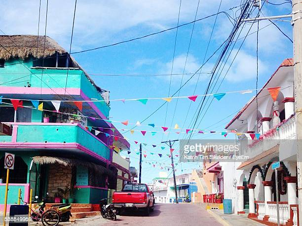 prayer flag hanging amidst buildings in city - isla mujeres ストックフォトと画像