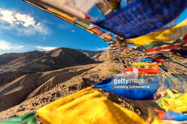 Prayer flags flicking on top of mountain at Lamayuru temple in Leh ladakh on the hill in mountain valley with blue sky