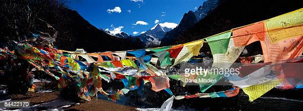 Prayer flags in the foreground of the mountain Chenadorje the deity of power one of three holy mountains for Buddhists in Yading a reserve in...