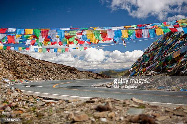prayer flags over gamta pass on the friendship highway between lhasa and gyantse. - merten snijders stockfoto's en -beelden