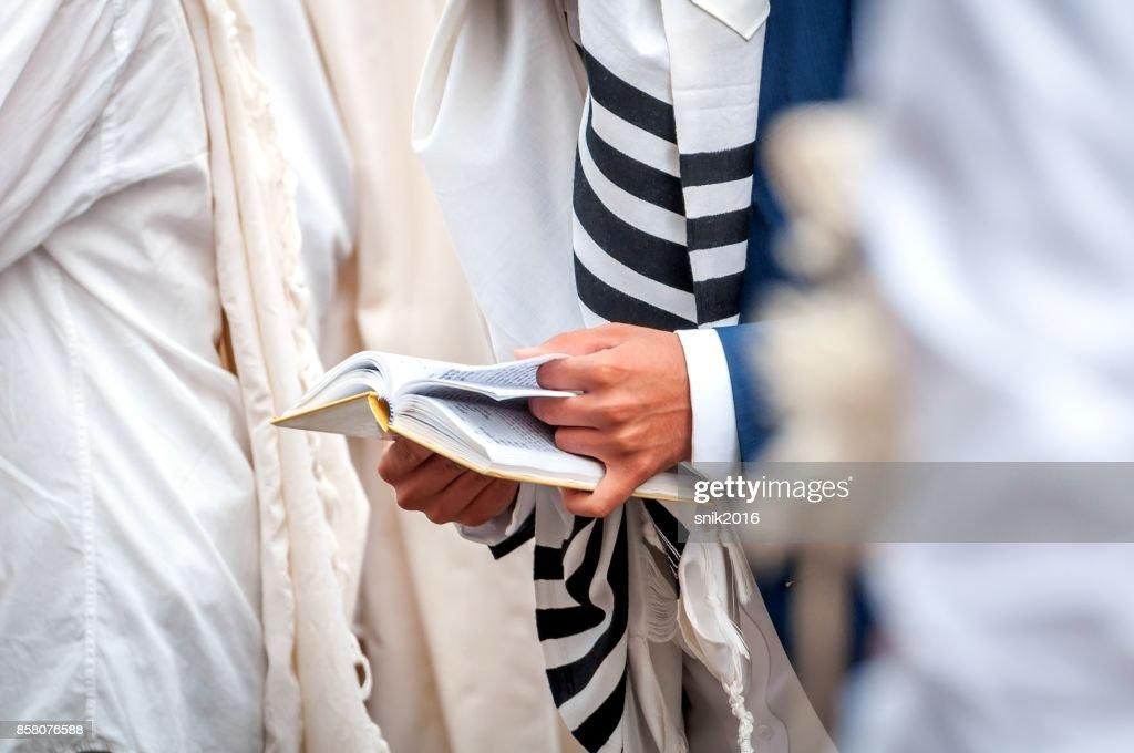Gebet. Chassid in traditioneller Kleidung. Tallis - jüdischen Gebetsschal. Hände halten ein Gebetbuch. Close-up. : Stock-Foto