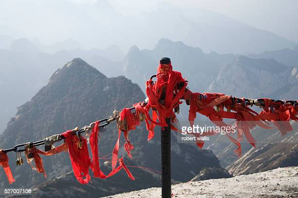 Prayer ribbons and 'prayer locks' are attached to a railing on Hua Shan Mountain a series of granite domes near Xian one of Taoism's five sacred...