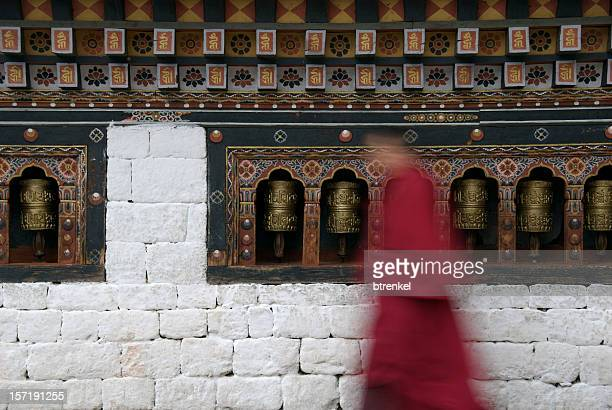 prayer wheels with monk - paro stock photos and pictures