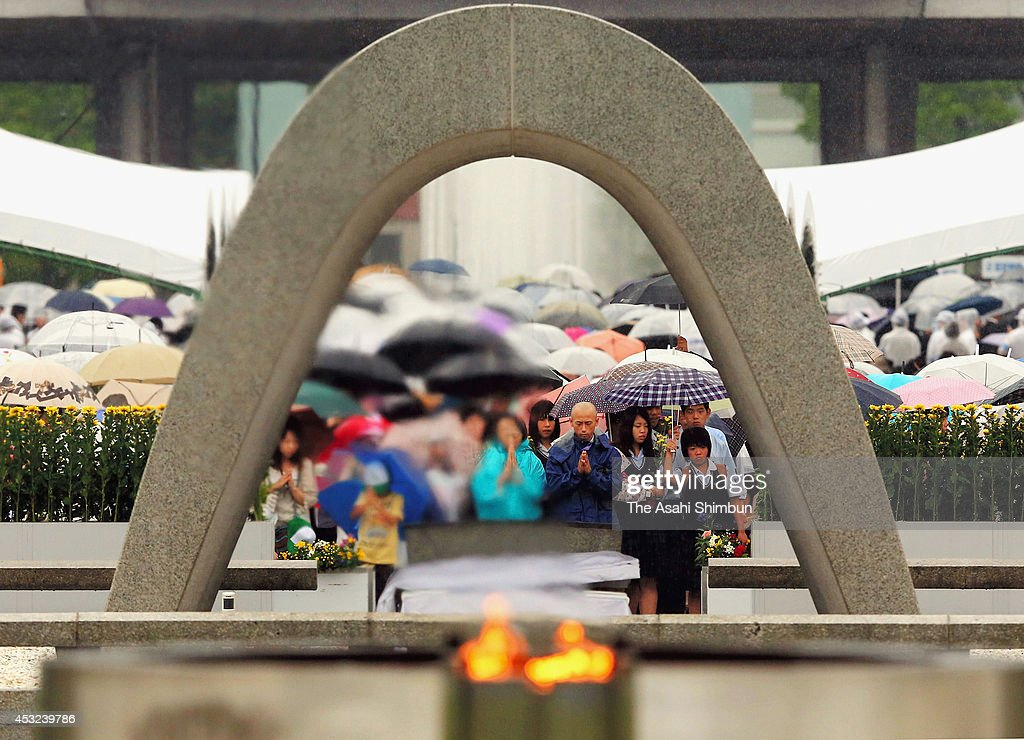 Prayers are offered in the rain to the memorial cenotaph at the Hiroshima Peace Memorial Park on August 6, 2014 in Hiroshima, Japan. Japan marks the 69th anniversary of the first atomic bomb that was dropped by the United States on Hiroshima on August 6, 1945.