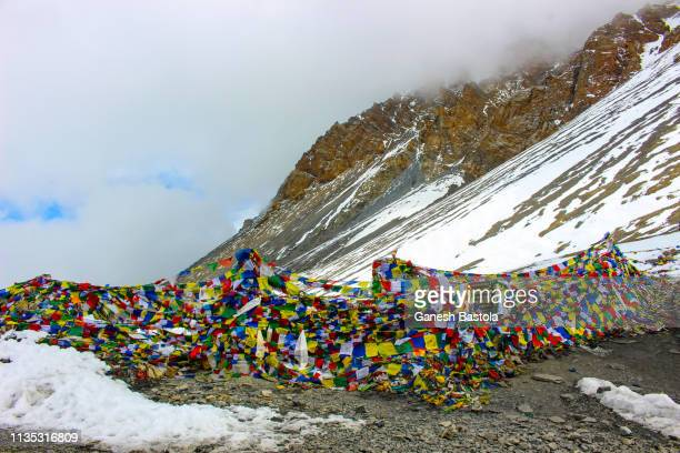 prayers flags in thorong-la pass - annapurna circuit stock photos and pictures
