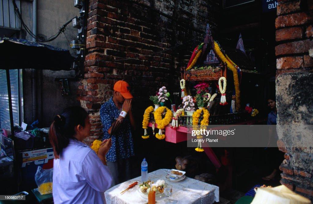 Praying at spirit house on Th Phra Athit, Banglamphu. : Stock Photo
