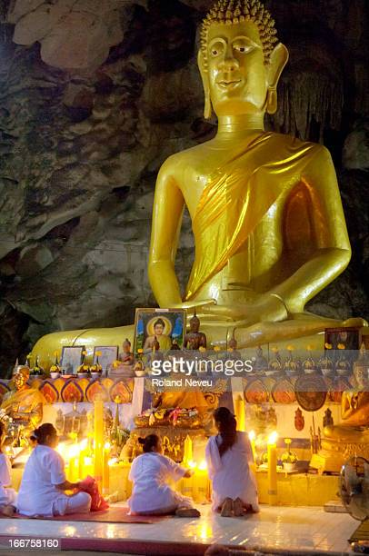 Praying at the foot of the big Buddha statue inside the Wat Tham Bo Ya cave During Khao Phansa anyone in Thailand can go to meditate in a pagoda or...
