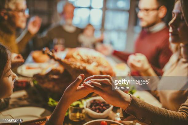praying before thanksgiving lunch! - religious blessing stock pictures, royalty-free photos & images