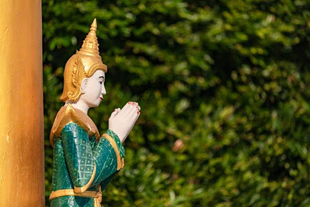 A Praying Buddha Statue With Folded Hands In A Temple Against A Natural Background In Myanmar