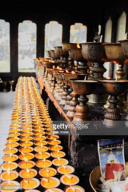 praying candles and brushed metal pots in zangdhopelri monastery - ipek morel stock pictures, royalty-free photos & images