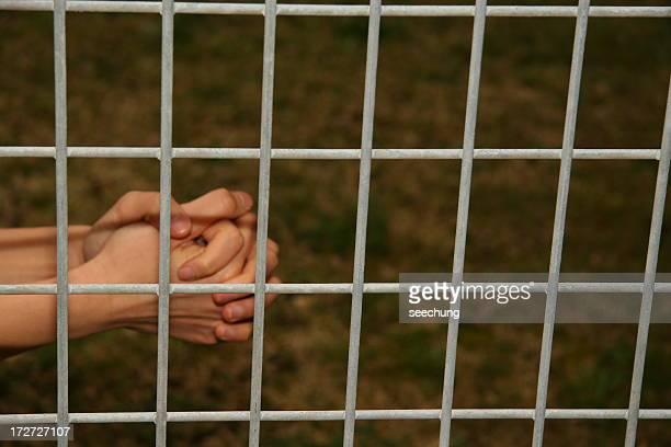 rezar manos detrás de la barra - federal prison fotografías e imágenes de stock