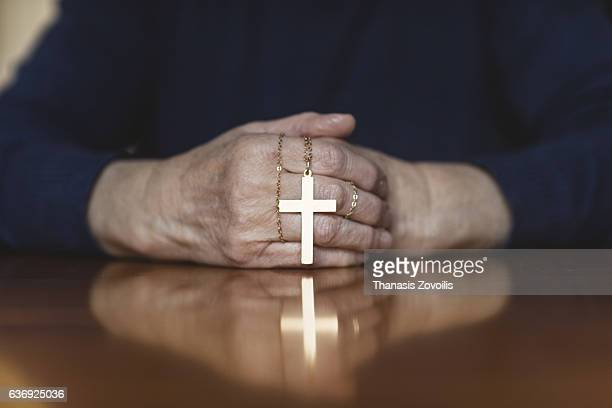 praying hands of woman with a cross on wooden desk - katholicisme stockfoto's en -beelden