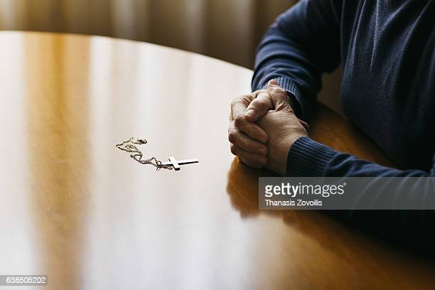 praying hands of woman with a cross on wooden desk - cristianesimo foto e immagini stock