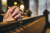 Praying hands with rosary in church