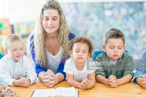 beten in der sonntagsschule - sonntag stock-fotos und bilder