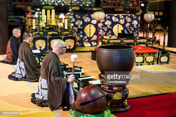 Praying Monks, with Iron Gong temple in Kyoto, Japan