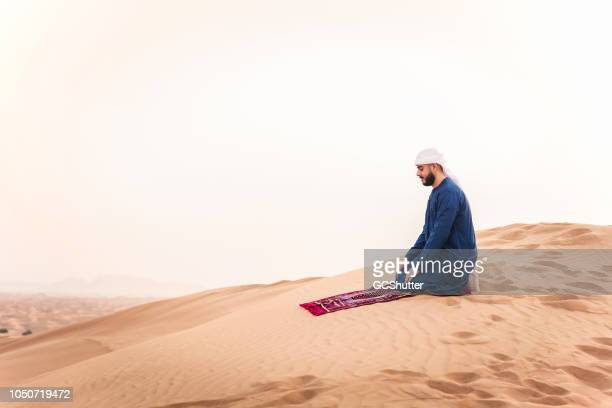praying on the sand dunes - bahrain national day stock photos and pictures